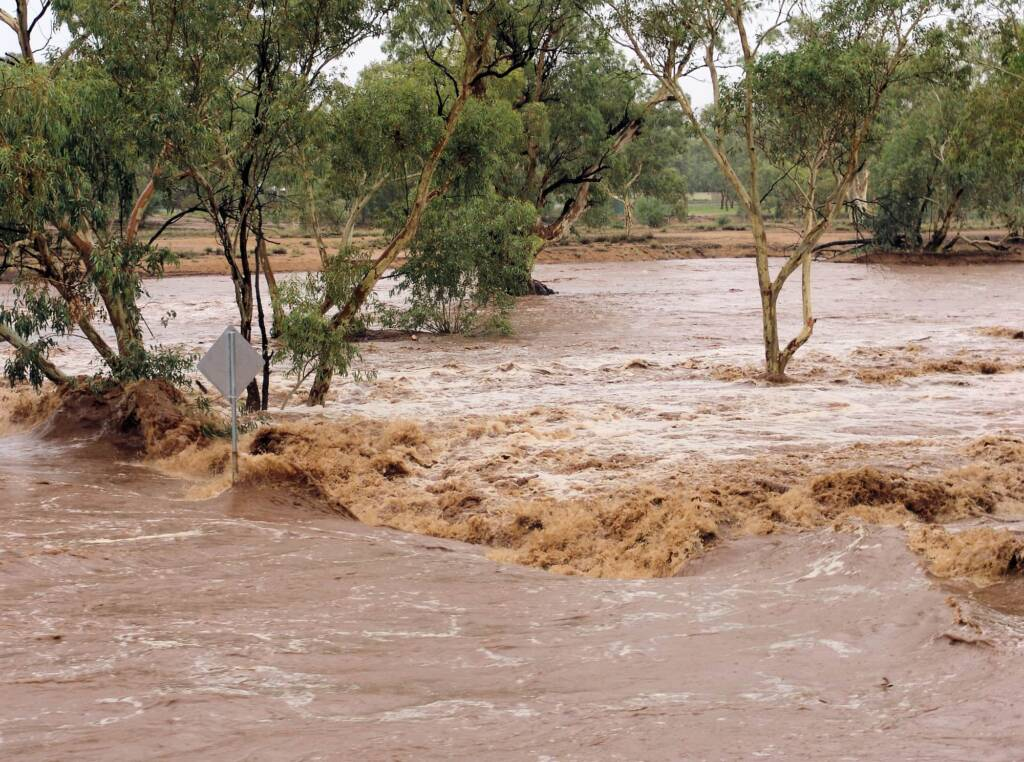 Water flowing swiftly over Undoolya Road causeway down the Todd River, Alice Springs, 9 Jan 2010