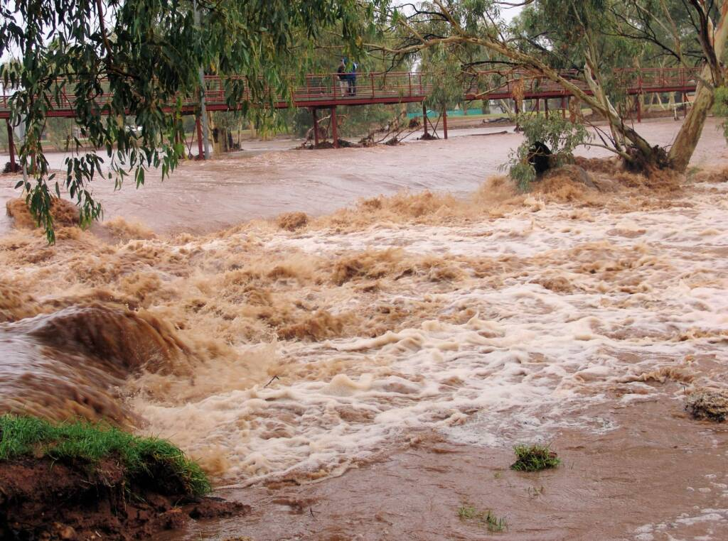 Water flowing swiftly over Undoolya Road causeway down into the Todd River, Alice Springs, 9 Jan 2010